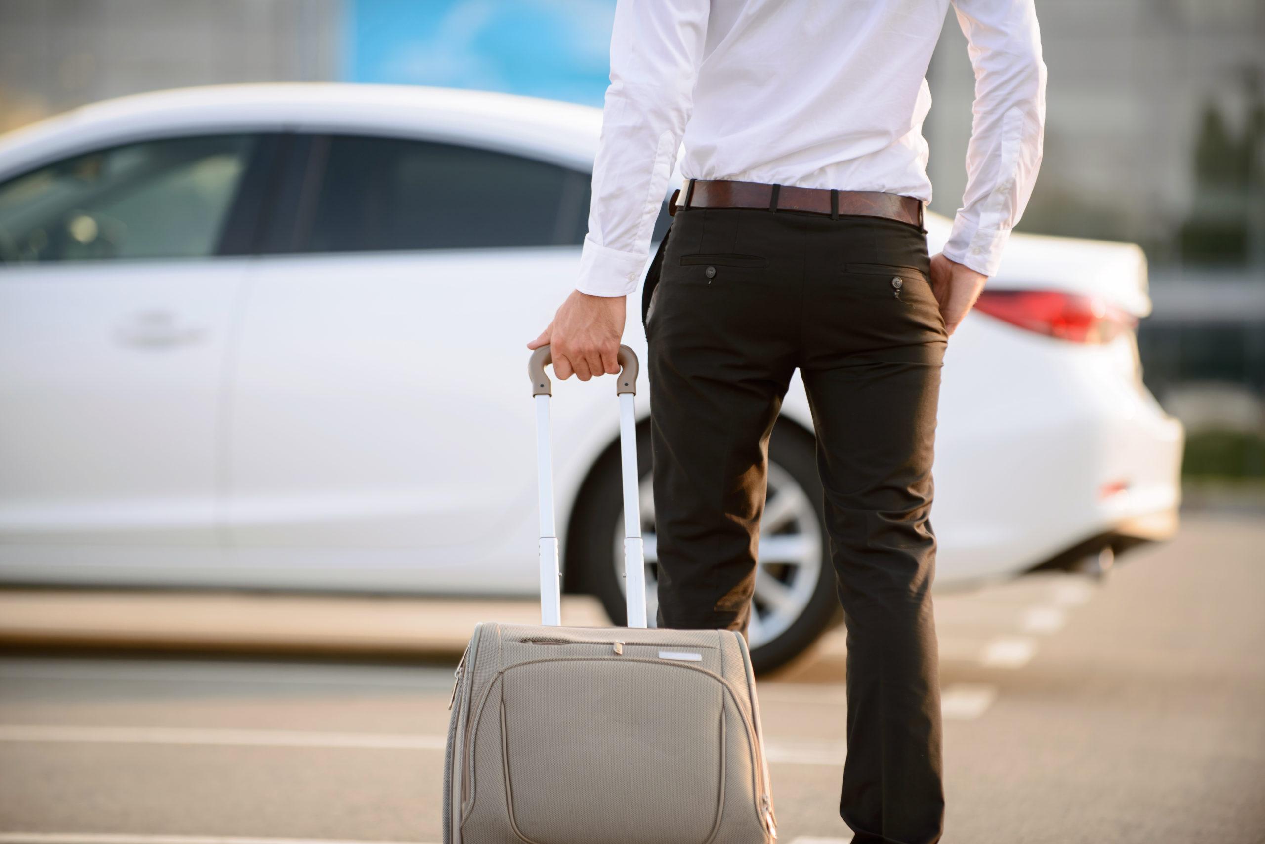 Mann mit Koffer vor Auto